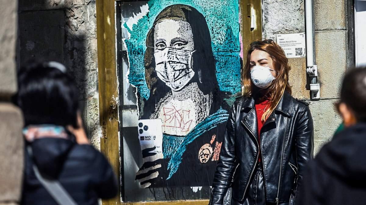 Εικόνα νεαρής γυναίκας με μάσκα μπροστά από γκράφιτι της Μόνα Λίζα να φοράει μάσκα